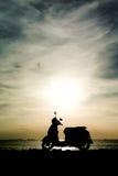 Vespa de la silueta en la playa Imágenes de archivo libres de regalías