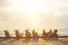 Vespa de la silueta en la playa con el fondo de la puesta del sol Fotografía de archivo
