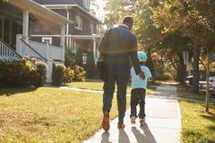 Vespa de Walking Son On del padre del hombre de negocios a la escuela foto de archivo libre de regalías