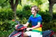 Vespa del montar a caballo del adolescente Muchacho en la motocicleta Fotografía de archivo