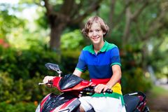 Vespa del montar a caballo del adolescente Muchacho en la motocicleta Foto de archivo