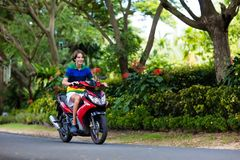 Vespa del montar a caballo del adolescente Muchacho en la motocicleta Imágenes de archivo libres de regalías