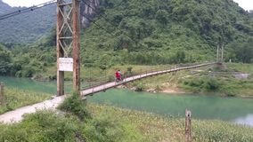 Vespa del paseo del individuo de la muchacha a lo largo de puente colgante estrecho metrajes