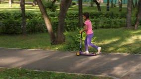 Vespa del paseo del pequeño niño en parque el día de verano Juego lindo de la muchacha al aire libre Ocio activo y deporte al air almacen de video