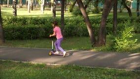 Vespa del paseo del pequeño niño en parque el día de verano Juego lindo de la muchacha al aire libre Ocio activo y deporte al air almacen de metraje de vídeo