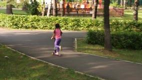 Vespa del paseo del pequeño niño en parque el día de verano Juego lindo de la muchacha al aire libre Ocio activo y deporte al air metrajes