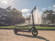 Vespa eléctrica en Sunny Park con la fuente fotografía de archivo
