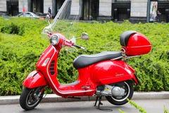 Vespa Italiaanse rode autoped in de straat in Milaan Stock Afbeeldingen