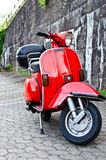 Vespa moped. Standing next to a wall Stock Images