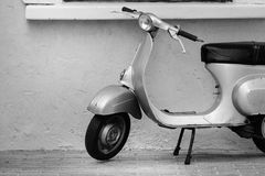 Vespa motorcycle parked next to the wall. Chonburi, Thailand - December 18, 2016: Old classic retro Vespa motorcycle parked next to the wall, black and white Stock Images