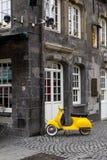 Vespa retra amarilla del estilo parqueada Fotos de archivo
