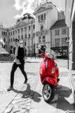 Vespa roja en escena urbana blanco y negro Fotografía de archivo