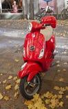 Vespa rojo parqueado en la calle de Munich Foto de archivo