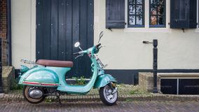 Vespa scooter in front of a house Stock Images
