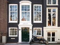 Vespa scooter stands parked near old living house in Amsterdam Royalty Free Stock Photos