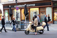 Vespa with woman rider in front of Europe Starbucks Stock Photo