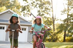 Vespa y bici de With Brother Riding de la hermana en la calzada en casa fotos de archivo