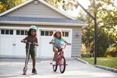 Vespa y bici de With Brother Riding de la hermana en la calzada en casa fotografía de archivo