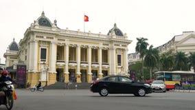 Vespas, ciclomotores, coches, tráfico y gente fuera del teatro de la ópera de Hanoi, Hanoi, Vietnam metrajes