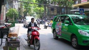 Vespas, coches, tráfico, turistas, y gente en las calles cuartas viejas del capital, Hanoi, Vietnam almacen de video