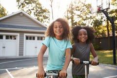 Vespas de Brother And Sister Riding en la calzada en casa imágenes de archivo libres de regalías