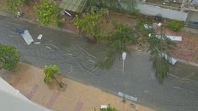 Vespas de la impulsión de la gente a lo largo del camino inundado después del tifón