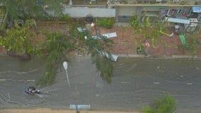 Vespas de la impulsión de los hombres a lo largo de la calle inundada contra árboles derribados