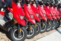 Vespas o motocicletas rojas para la venta o el alquiler en fila Fotografía de archivo
