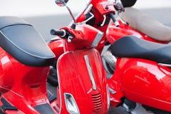 Vespas rojas que parquean en las calles foto de archivo libre de regalías
