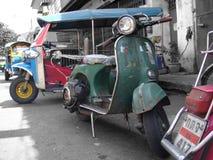 Vespas y Tuk-Tuks parquearon en un callejón de Bangkok imagenes de archivo