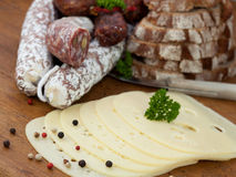 Vesper. Sausage and cheese on a wooden board Stock Photography