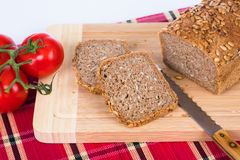 Vesper. Tomatoes and fresh cut loaf of fullgrain bread Royalty Free Stock Images