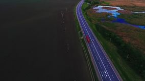 Vespers highway, the movement of cars on the highway. Red truck moving. Asphalt road in Russia, Krasnodar. Air view of. The Lotus lake. Shooting with stock video footage