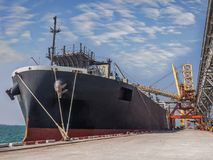 Bulk vessel loading onboard. Vessel alongside at thailand port and loading bulk cargo royalty free stock photography
