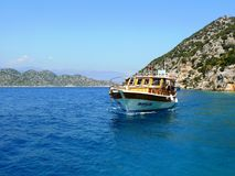The vessel with excursion and vacationers sailing in the Gulf on the Mediterranean. Turkey. The vessel with excursion and vacationers sailing in the Gulf on the Stock Photo