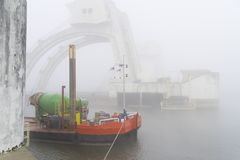 Vessel in the mist. Misty image of a red vessel in front of the Driel weir in the netherlands stock photos