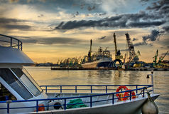 Vessel at the port after storm. Cruise vessel moored at the port near portal cranes, moody sky Royalty Free Stock Image