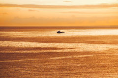 Vessel is sailing in the ocean at sunrise. Marine vessel is sailing in the ocean at sunrise Stock Photo
