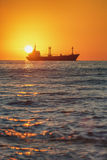 Vessel sailing in the sea near the harbor on beautiful sunrise Royalty Free Stock Image