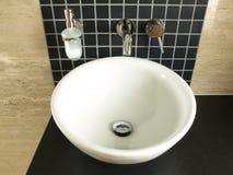 Vessel sink in a modern bathroom. Vessel porcelaine sink on a black granite countertop stock photo