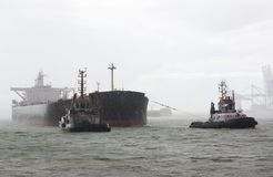 Vessel and tugboats in heavy rain Stock Photography