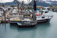 Vessels tied at a jetty in valdez with mountains in the background. Fishing boats waiting for the salmon to start running at a busy harbour in alaska Stock Photos
