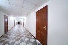 Vestíbulo brillante largo con las puertas y el piso de madera Imagen de archivo