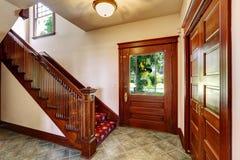 Vestíbulo de la entrada con la escalera de madera Foto de archivo libre de regalías