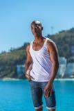 Veste branca vestindo do homem negro africano e calças de brim curtos azuis Imagem de Stock