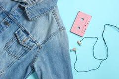 Veste de jeans, cassette sonore, écouteurs de vide sur le fond en pastel bleu Rétros médias, mélomane, 80s Vue supérieure, config photo stock