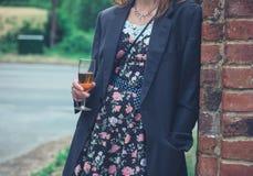 Veste de port de jeune femme et vin potable photo libre de droits