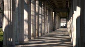 Veste de port femelle de camouflage de métis d'adolescente de jeune femme, marchant par le passage de colonnes au cours de la jou banque de vidéos