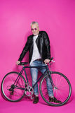Veste en cuir de port à la mode de sourire et sunglesses d'homme supérieur se tenant avec la bicyclette Photos libres de droits