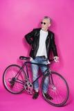 Veste en cuir de port à la mode et sunglesses d'homme supérieur se tenant avec la bicyclette Photographie stock